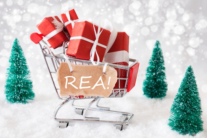 Trolly With Christmas Gifts And Snow, Text Rea. Trollye With Christmas Presents Or Gifts. Snowy Scenery With Snow And Trees. Sparkling Bokeh Effect. Label With stock photo