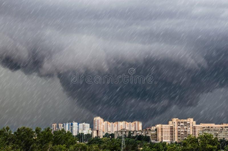 Tromben tratt fördunklar under en åskväder en hällregnhällregn över staden royaltyfri foto