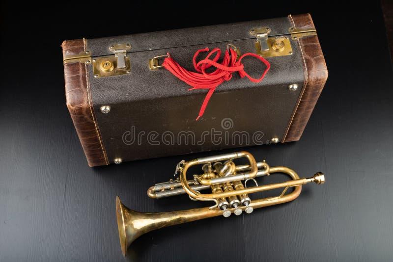 Trombeta coberta velha da pátina em um caso Um instrumento musical do vento histórico e uma mala de viagem imagem de stock royalty free