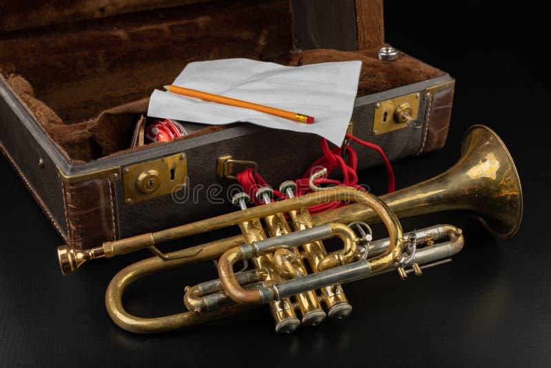 Trombeta coberta velha da pátina em um caso Um instrumento musical do vento histórico e uma mala de viagem foto de stock