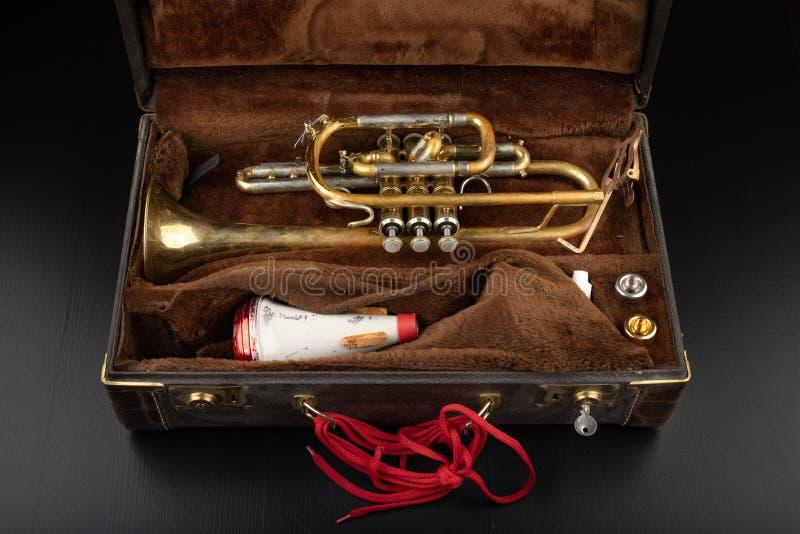 Trombeta coberta velha da pátina em um caso Um instrumento musical do vento histórico e uma mala de viagem imagens de stock