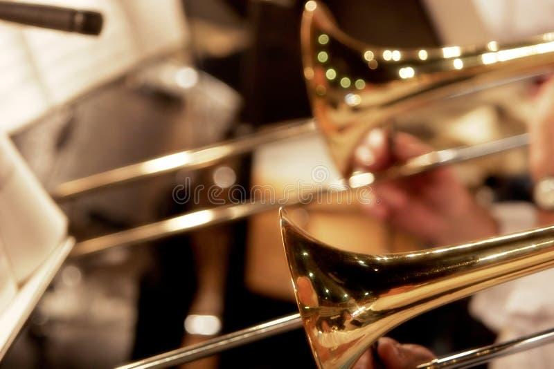Trombones che giocano in una grande fascia (fuoco poco profondo). fotografie stock