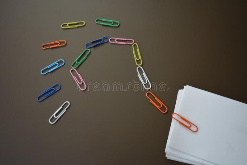 Trombones colorés présentés avec un point d'interrogation et avec des feuilles de livre blanc pour enregistrer sur un fond mat br image libre de droits