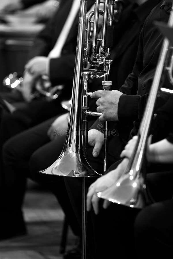 Trombones dans les mains des musiciens dans l'orchestre photographie stock