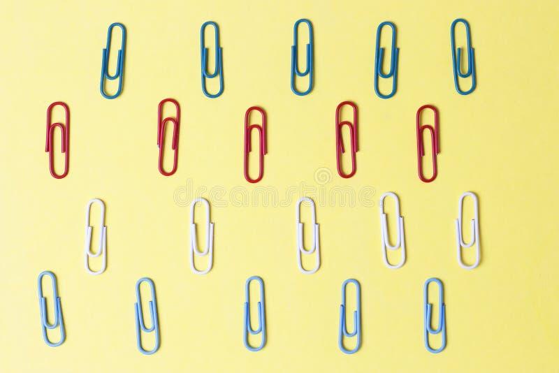 Trombones multicolores sur un fond jaune, concept de bureau images stock