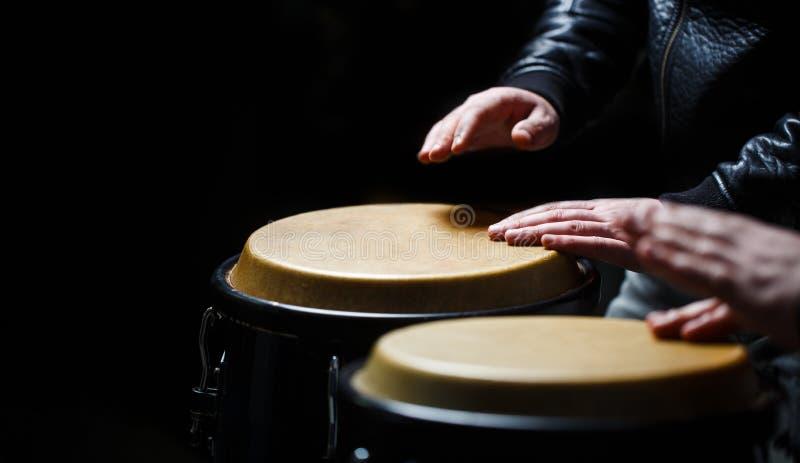 Trommel H?nde eines Musikers, der an spielt, bongs Der Musiker spielt den Bongo Schlie?en Sie oben von der Musikerhand, die Bongo stockfotos