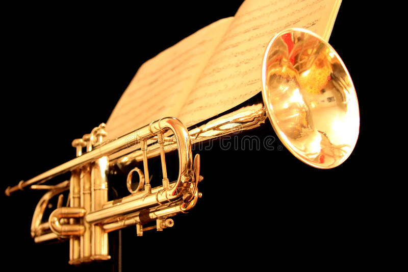 Trompeta de oro con partitura en fondo negro imagenes de archivo