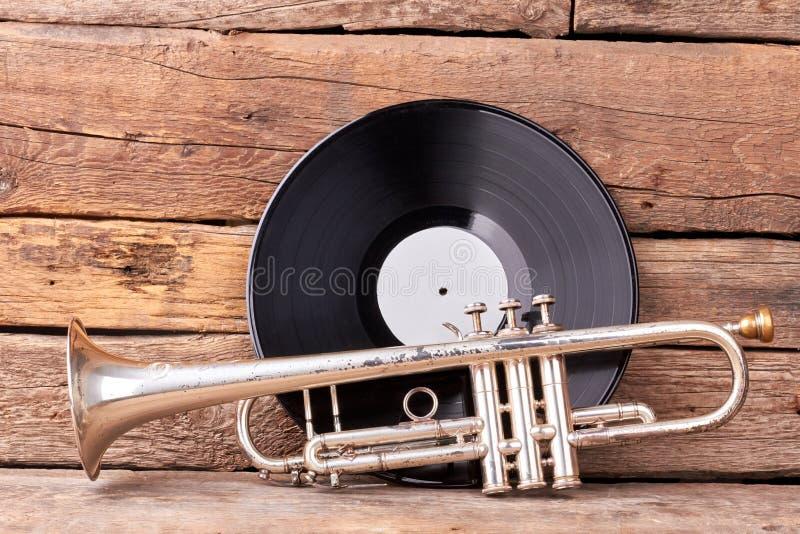 Trompete und Plastikaufzeichnung auf hölzernem Hintergrund lizenzfreie stockfotos
