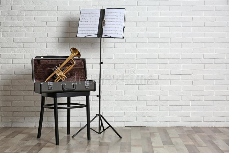 Trompeten-, Stuhl-, Fall- und Anmerkungsstand mit Musikblättern nahe Backsteinmauer stockfotografie