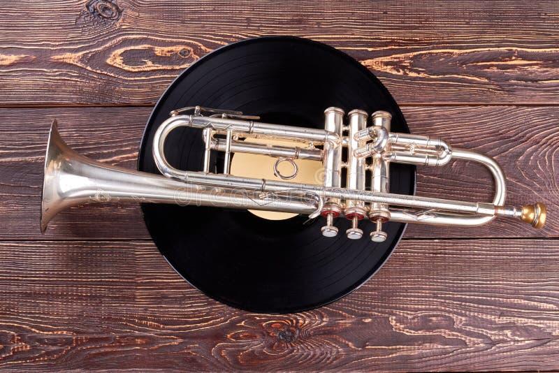 Trompeten- und Vinyldiskette auf hölzernem Hintergrund lizenzfreies stockfoto