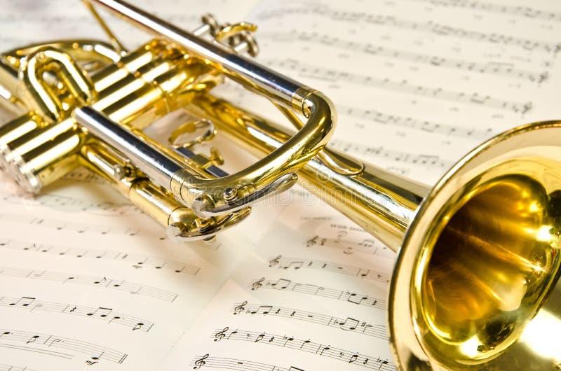 Trompette d'or brillante se trouvant sur la musique de feuille photo libre de droits