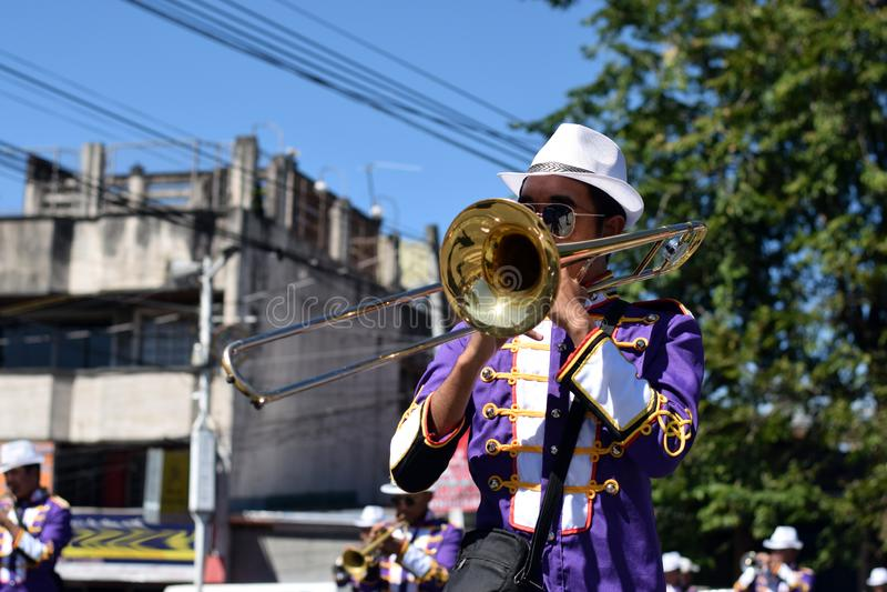 Trompette masculine de jeu de membre du groupe pendant le cortège de festivité de ville image libre de droits