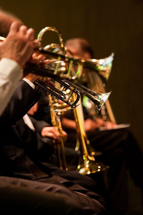Trompetten in de handen van de musici in het orkest royalty-vrije stock afbeeldingen