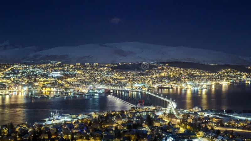 Tromsø på natten, sikten in mot bron och arktiskdomkyrkan royaltyfri foto