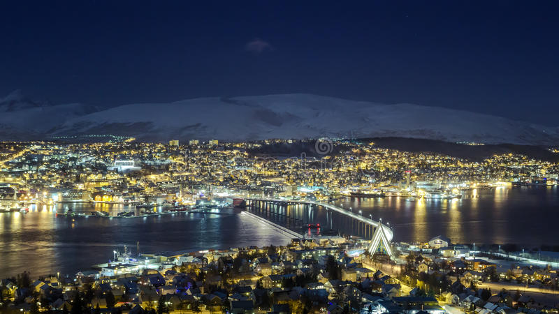 Tromso city night panorama, view from the mountains towards bridge and Arctic Cathedral. Tromso at night, view towards bridge, Arctic Cathedral and surrounding royalty free stock photo