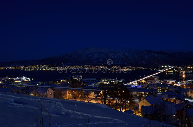 Tromso city at winter snowy night with light,traffic,fjord and motion with mainland stock image