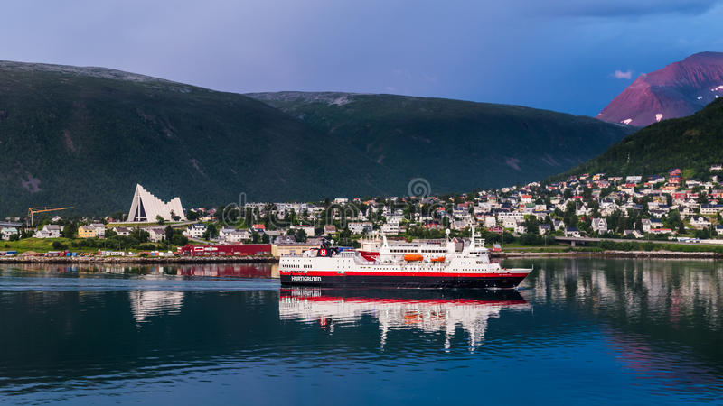 TROMSO, FINLAND - JULY 26, 2016: the Hurtigruten ship navigating into Tromso Norway. Skyline with Arctic Cathedral and the Hurtigruten ship navigating into the stock photography