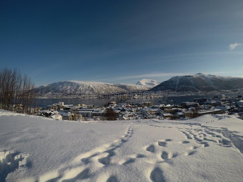 TROMSOE NORGE - MARS 4, 2017: Video för överblick för Tromsoe stadsö med biltrafik över tromsoeöbron, snöig mountai royaltyfri foto