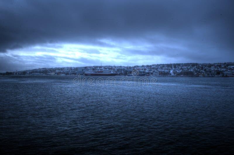 Tromsoe stadsö under dimma och mist för tungt väder över hus och blått fjordlandskap arkivbilder