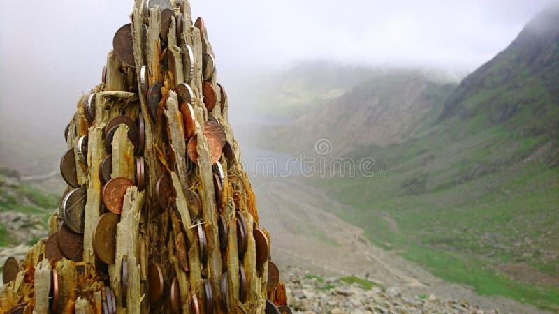 Tronçon d'arbre chanceux d'argent dans le premier plan regardant en arrière en bas de la montagne sur la traînée de PYG sur le bâ image stock