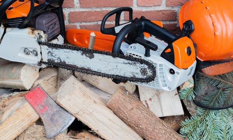 Tronçonneuse conduite par essence sur une pile en bois images libres de droits
