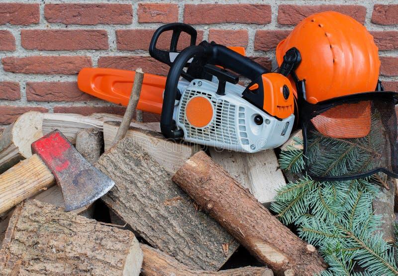 Tronçonneuse conduite par essence sur une pile en bois photo stock