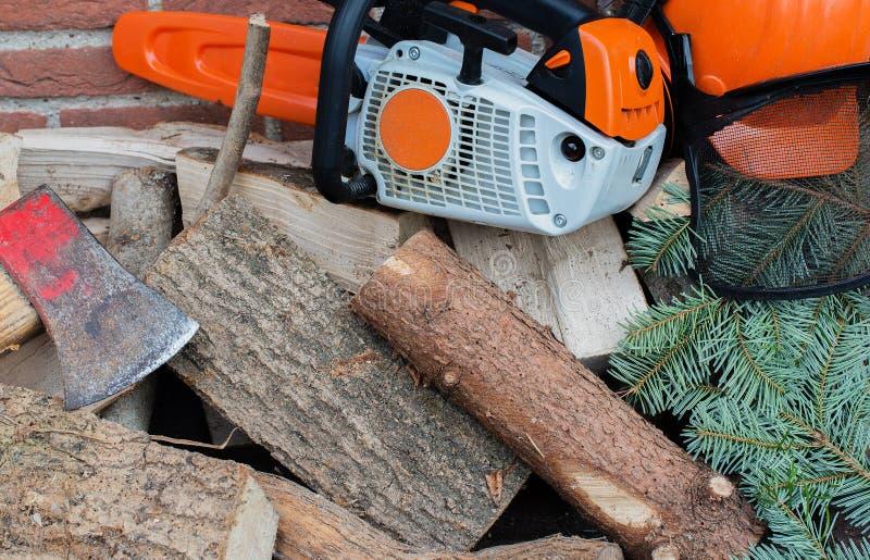Tronçonneuse conduite par essence sur une pile en bois photos stock