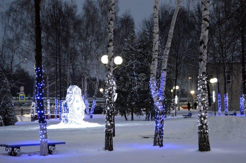Troncos das árvores em bulbos e em festões do Natal, fotografia de stock royalty free
