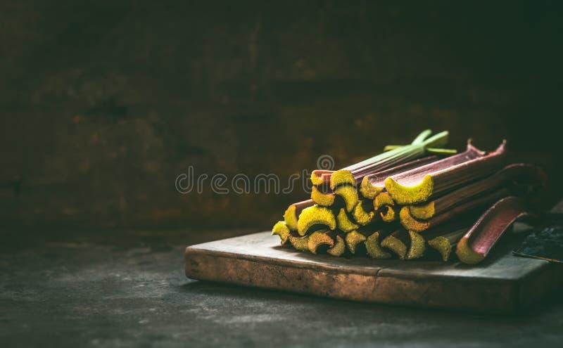 Troncos del ruibarbo en la tabla de cocina rústica oscura Copie el espacio Alimento biológico estacional Consumici?n y el cocinar foto de archivo