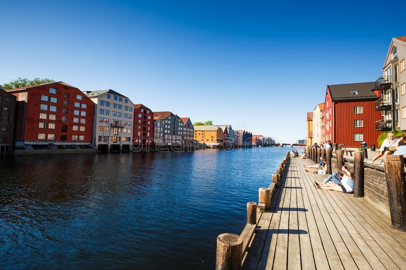 Trondheim in Norway. Trondheim, Norway -June 9, 2018 - Colorful old houses at the Nidelva river embankment, people relaxing on old wooden pier royalty free stock photo