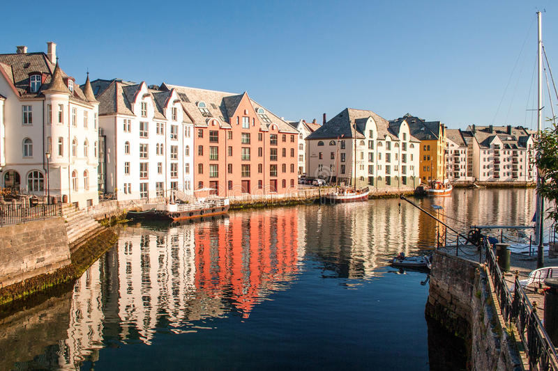 Trondheim, Norway. Multicolored houses in the river bank are ref. The sunny weather in summer day supplements reflection of houses with bright blue reflection of royalty free stock image