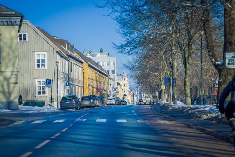 TRONDHEIM, NORWEGEN - 6. APRIL 2018: Ansicht im Freien der Straße mit einigen Autos parkte das umgeben mit traditionellem Skandin stockfotografie