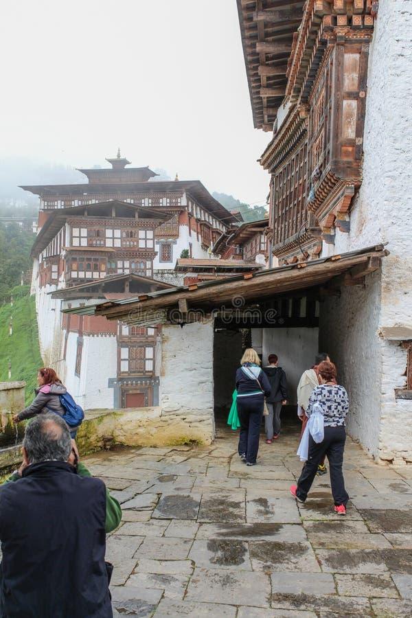 Trongsa, Bhután - 13 de septiembre de 2016: Grupo turístico que camina en Trongsa Dzong, Bhután foto de archivo