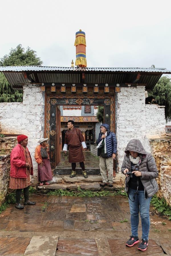 Trongsa, Bhután - 13 de septiembre de 2016: Grupo turístico que espera con los locals en Trongsa Dzong en un día lluvioso, Bhután fotografía de archivo libre de regalías