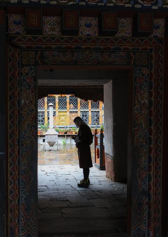 Trongsa, Bhután - 13 de septiembre de 2016: Hombre butanés en el vestido tradicional que se coloca en la entrada en Trongsa Dzong imágenes de archivo libres de regalías