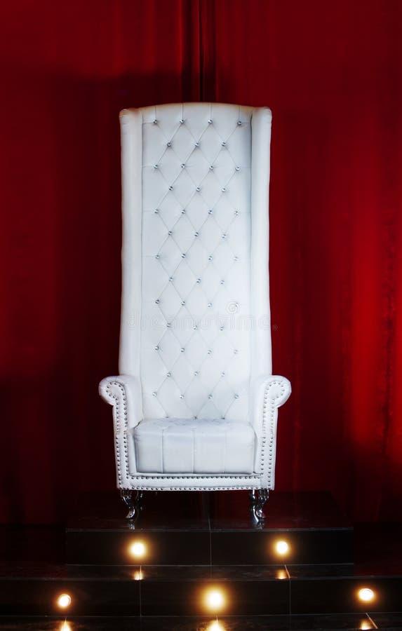 Trono blanco en un fondo rojo, silla con el alto trasero, posición elevada fotografía de archivo