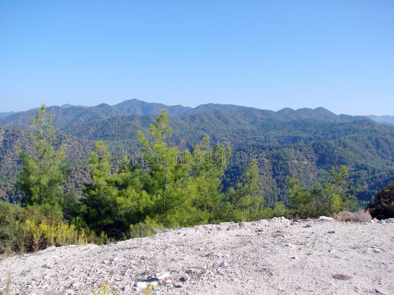 Troodos Mountains Cyprus. Landscapes of mountain horizons at an altitude of 500 m above sea level. A view from the sun-lighted mountain road to the sky blue stock photo
