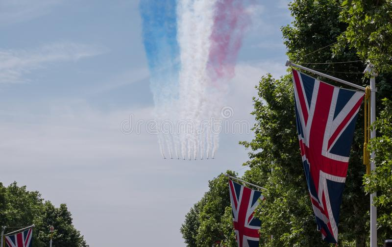 Trooping of the Colour parade, above Buckingham Palace. Nine Red Arrow planes fly in formation. Union jack flags in foreground royalty free stock image