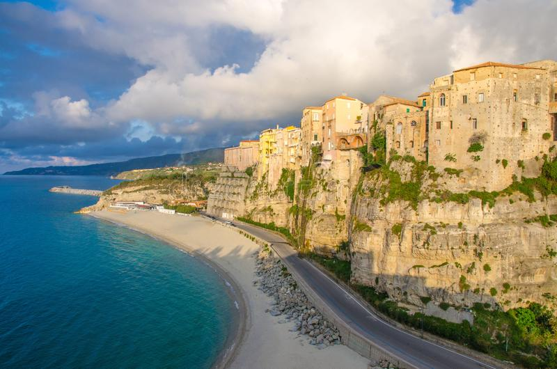 Tropea town and Tyrrhenian Sea beach, colorful buildings on top of high big steep rock cliff, view from Sanctuary church of Santa stock photography