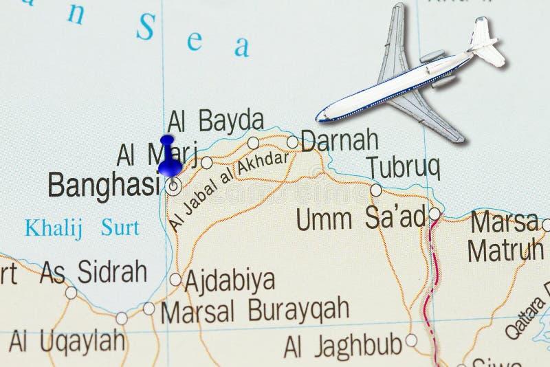 Tropece a Benghazi com avião do brinquedo e empurre o pino no mapa fotografia de stock