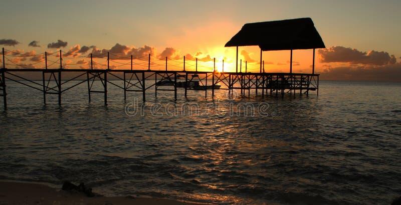Tropeninsel-Sonnenuntergang und Pier lizenzfreie stockbilder