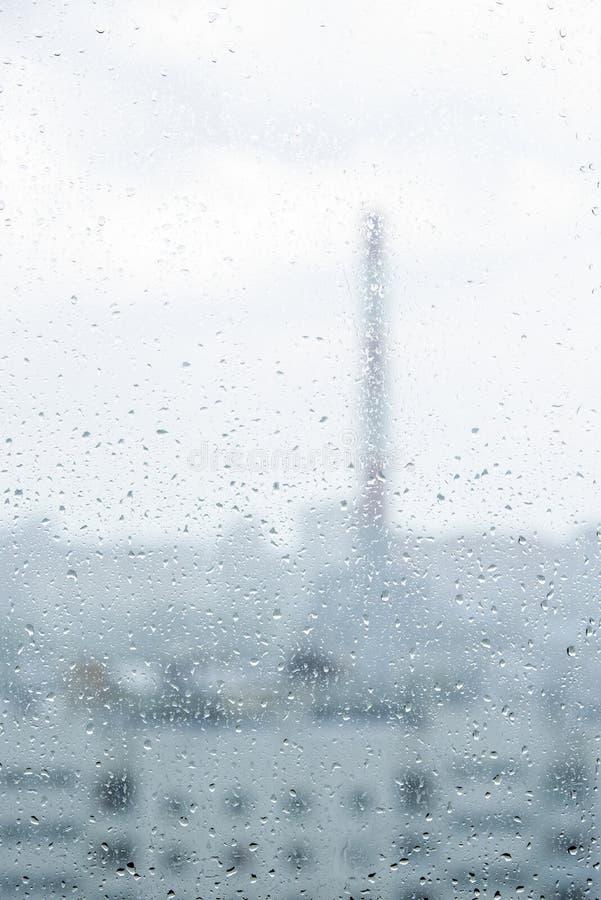 Tropfen auf dem Glas und eine Ansicht vom Balkon der Stadt lizenzfreie stockbilder