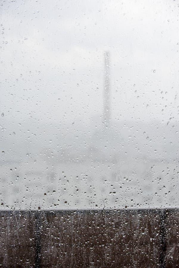 Tropfen auf dem Glas und eine Ansicht vom Balkon der Stadt stockbild