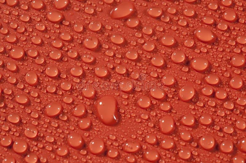 Tropfen auf orange Hintergrund lizenzfreies stockbild