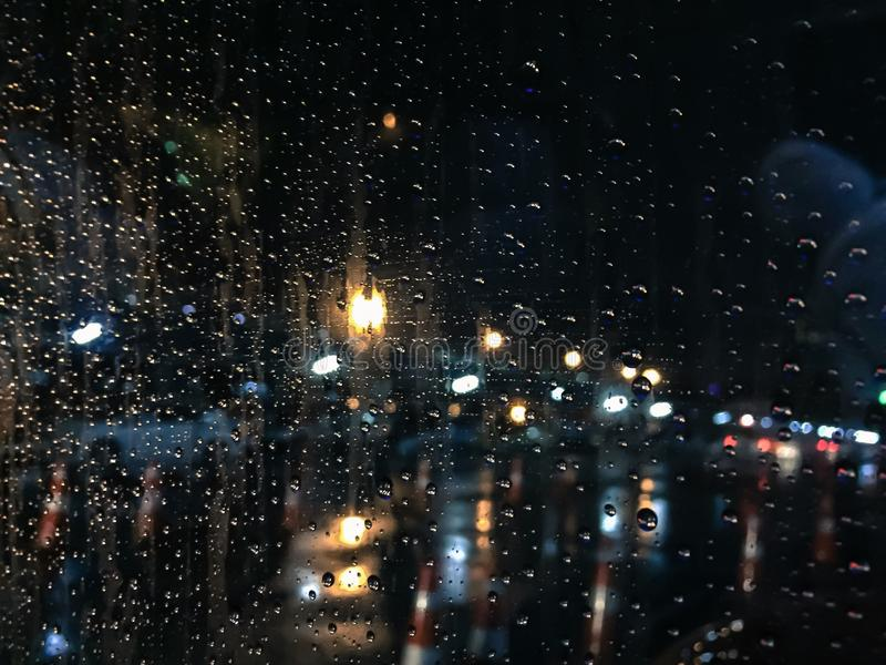 Tropfen des Regens auf blauem Glashintergrund nachts, das Licht vom Auto lizenzfreie stockfotografie