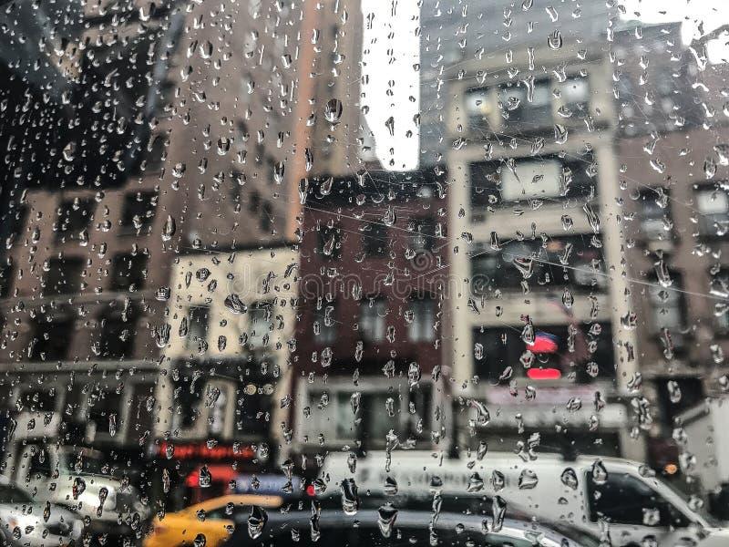 Tropfen des Regens auf einem Fenster mit einer Stadtansicht stockfotos