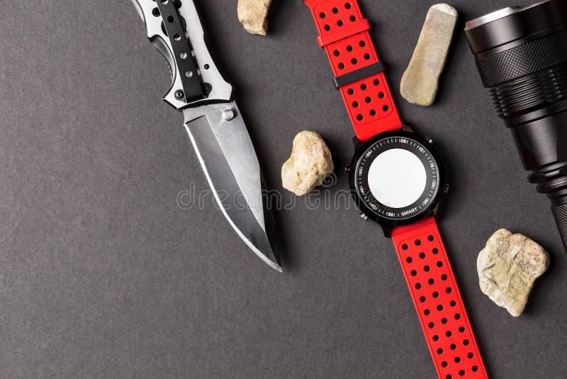 Tropiący przedmiot, składa łowieckiego nóż, czerwonego smartwatch i blac, fotografia royalty free
