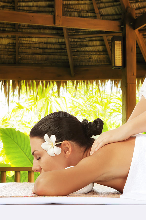 Tropic massage. Portrait of young beautiful woman on color back stock photography