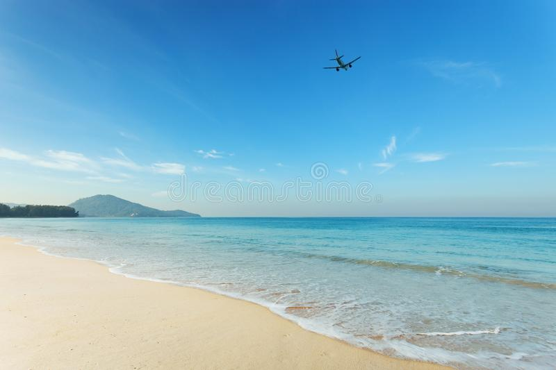 Tropical andaman seascape scenic off mai khao beach and wave crashing on sandy shore in phuket thailand with airplane takes off o. N sky,can be used for air stock photography