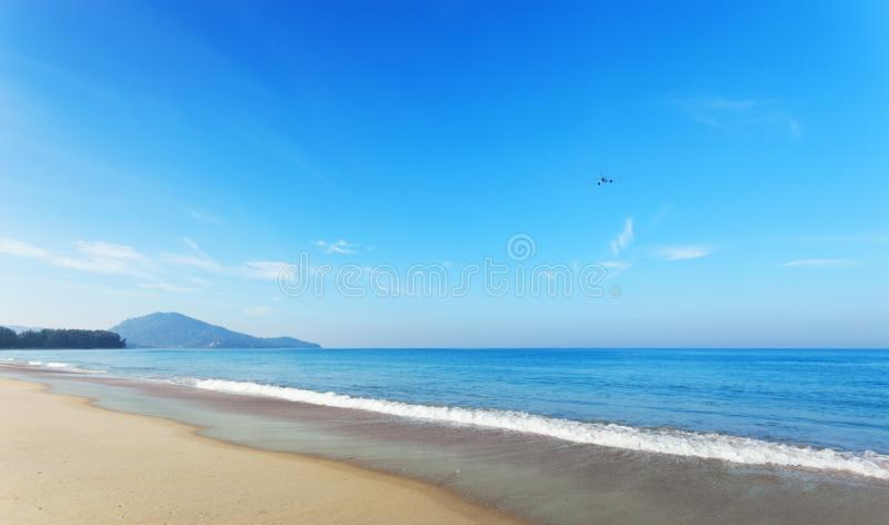 Tropical andaman seascape scenic off mai khao beach and wave crashing on sandy shore in phuket thailand with airplane takes off o. N sky in summer season stock image